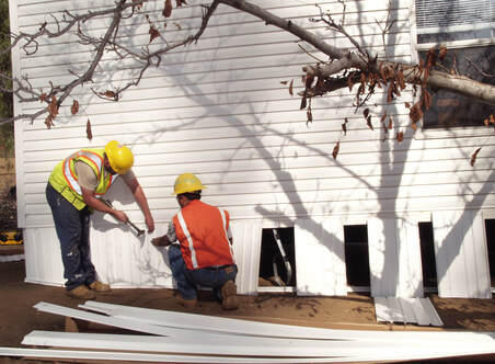 Picture of two workers installing skirting on a white mobile home.
