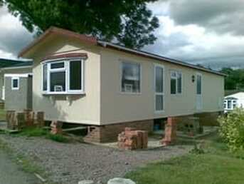 Picture of a tan colored mobile home with the brick skirting partially removed